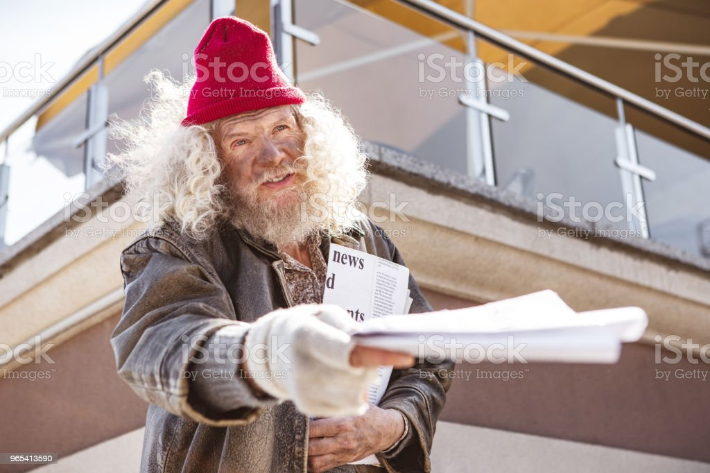 Nice aged man holding newspapers zbiór zdjęć royalty-free