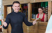 Nice athletic man talking to girl at reception while taking for rent surf equipment in surf club