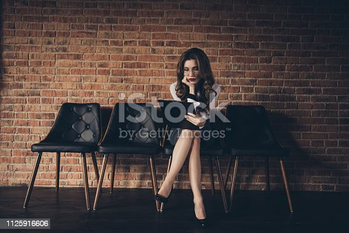 636681940istockphoto Nice attractive charming classy chic elegant lovely wavy-haired lady executive manager ceo boss chief long legs sitting on chair reading paper documents at work place station brick wall 1125916606