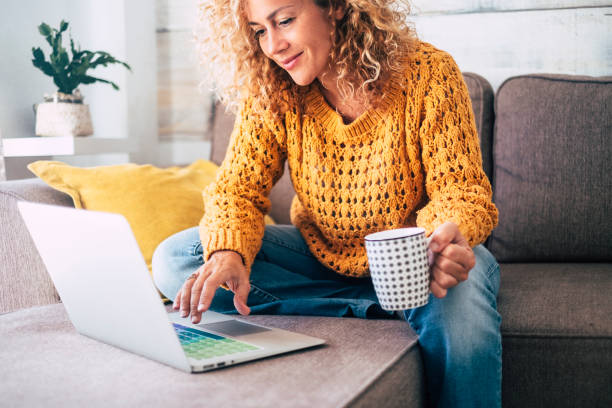 nice beautiful lady with blonde curly hair work at the notebook sit down on the sofa at home - check on oline shops for cyber monday sales - technology woman concept for alternative office freelance - donna foto e immagini stock