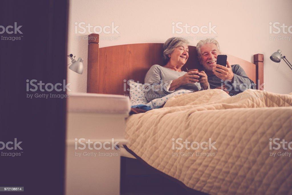 modelos hermosas bonita pareja de adultos mayores de 70 años divirtiéndose y disfrutar en la cama en su casa de habitación. mañana perezoso despertar sin prisa revisando correos electrónicos y contenido en el teléfono inteligente desayunando - foto de stock