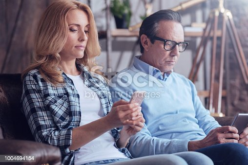 Internet addiction. Nice beautiful blonde woman holding a smartphone and using it while sitting on the sofa