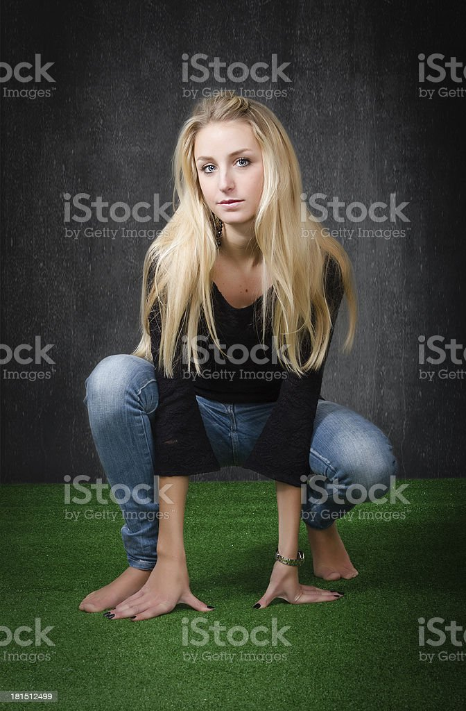 nice blonde squatting position on green park royalty-free stock photo