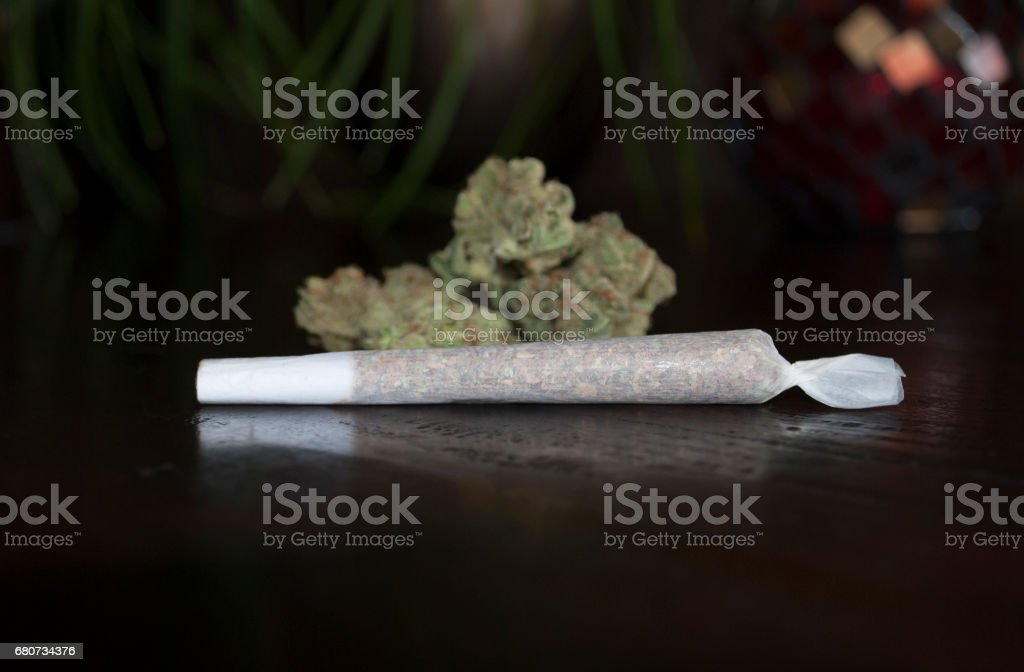 nice closeup of rolled marijuana weed joint on wooden background stock photo