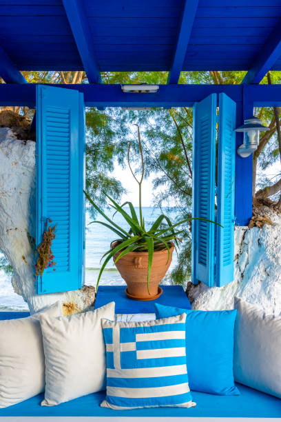 Nice composition of blue and white colors, window with sea view and greek flag, Crete, Greece stock photo