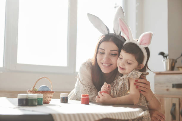 Schönes Tageslicht durch das Fenster. Mutter und Tochter in hästigen Ohren zur Osterzeit haben etwas Spaß in der Küche am Tag – Foto