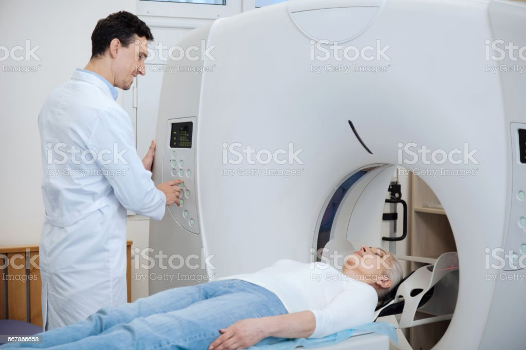 Nice delighted doctor doing tomography examination stock photo