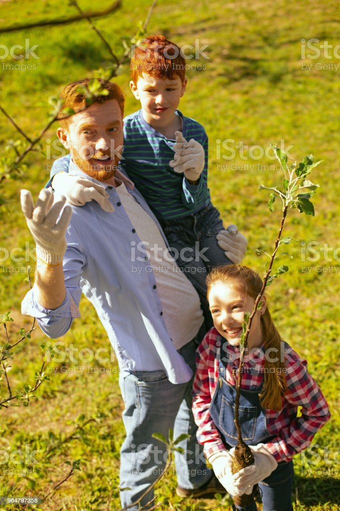 Nice delighted family working in the garden royalty-free stock photo
