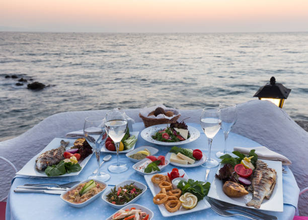 Nice dinner table ready for couple during sunset with peaceful seascape