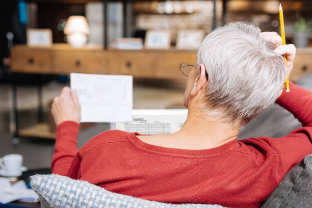 nice elderly man holding his head - social security check stock photos and pictures