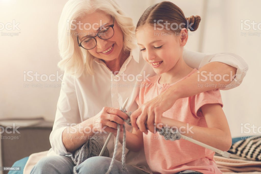 nice-elderly-woman-teaching-her-granddaughter-to-knit-picture-id936988238