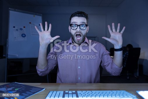istock Nice emotional man sitting in front of the computer screen 663249538