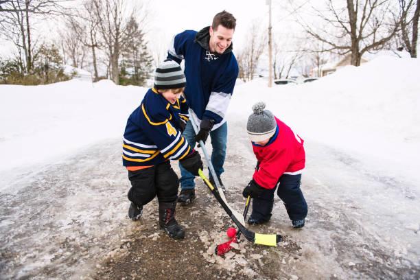 ein schönes vater und zwei söhne, hockey spielen - bruderschaft stock-fotos und bilder