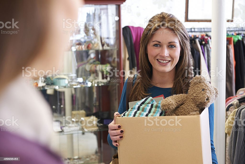 A nice female donating unwanted items to a charity shop stock photo