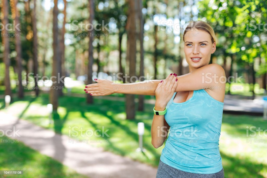 Nice fit young woman holding her hand stock photo