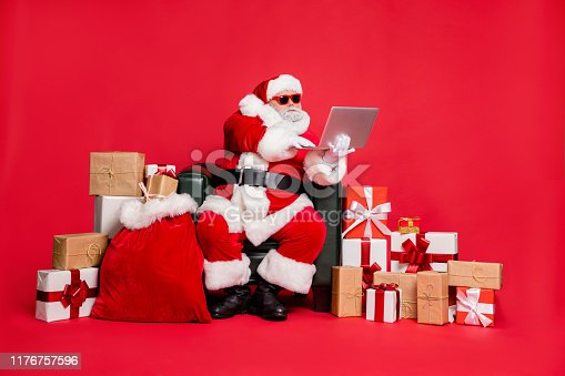 Nice focused hard-working fat bearded man sitting delivering many different, purchases shop delivery checking address list wi-fi clients isolated on bright vivid shine red background