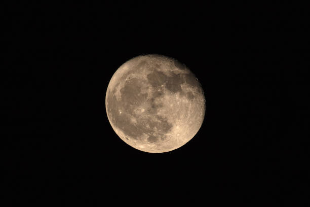 Nice full moon with soft yellow color an visible craters stock photo