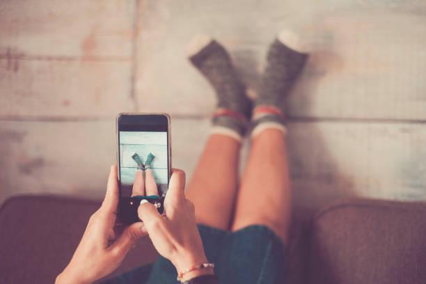 divertida hermosa chica tomar fotos a sus pies con calcetines locos - social media fotografías e imágenes de stock