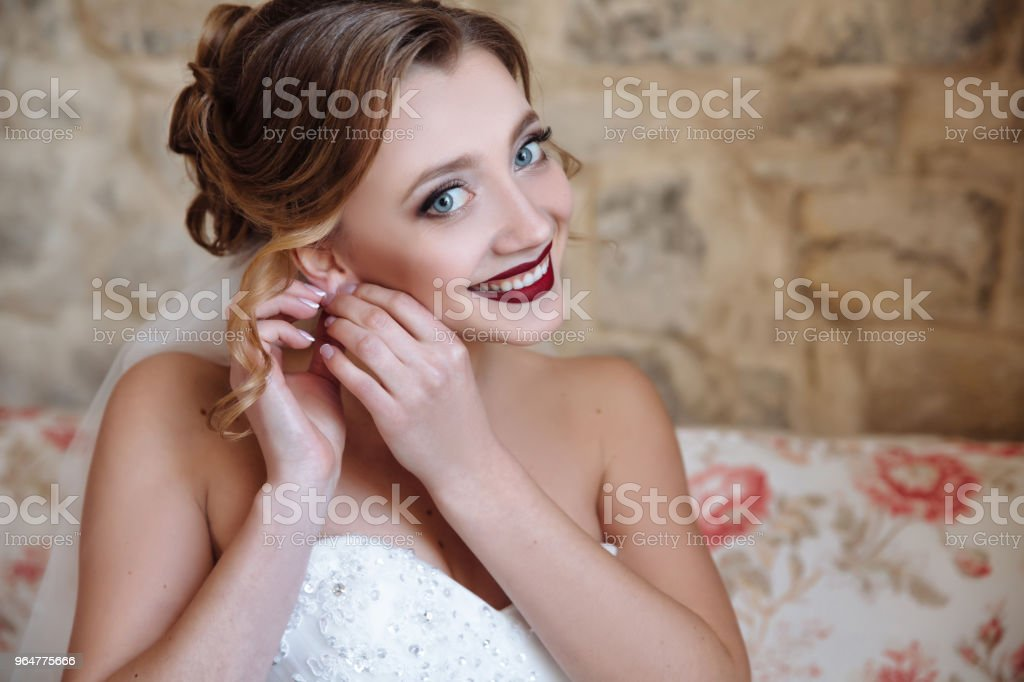 A nice girl in a wedding dress and veil puts on earrings and smiles broadly. The bride with big blue eyes, white even teeth and bright red lips royalty-free stock photo