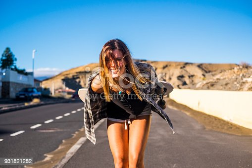 nice beautiful blonde girl with hair on face smiling at you. skateboard and nude legs for alternative lifestyle concept. vacation in Tenerife.