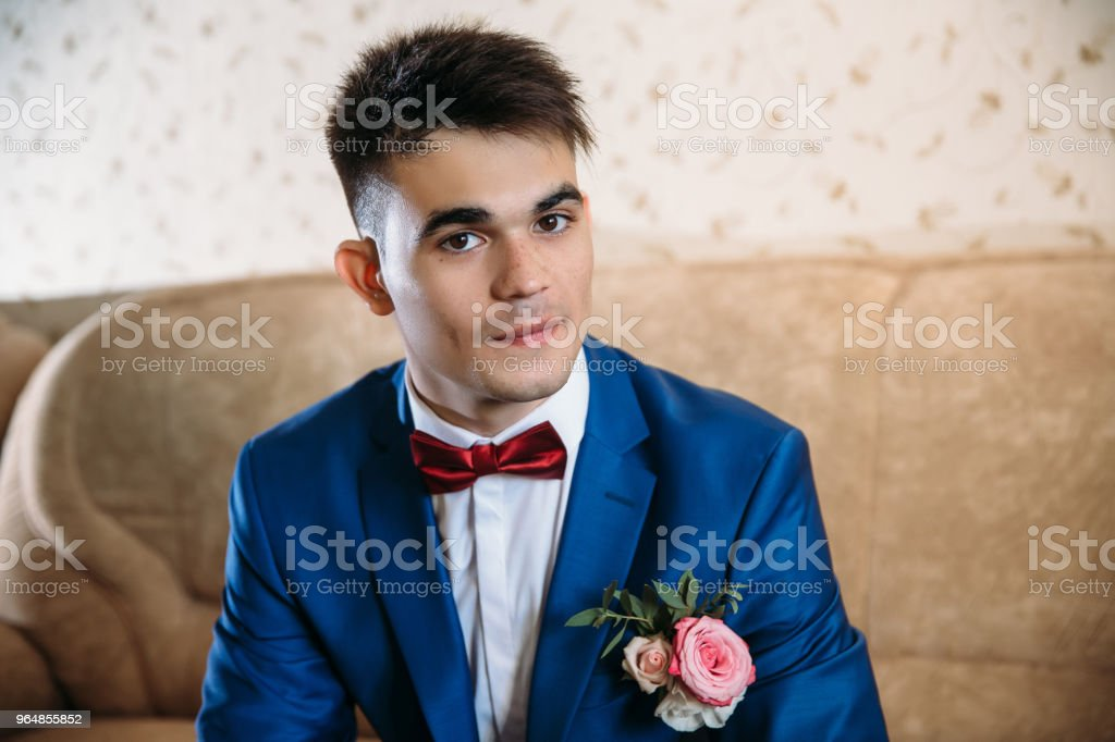 A nice guy with brown eyes and dark hair mysteriously looks into the camera. He is dressed in a beautiful blue suit with a boutonniere of roses and a white shirt with a red butterfly royalty-free stock photo