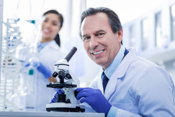 Nice happy man holding a microscope Professional device. Nice pleasant happy man holding a microscope and smiling while working in the biological lab dna purification stock pictures, royalty-free photos & images