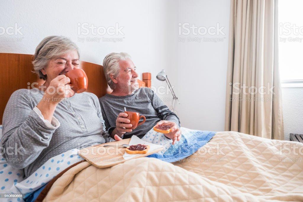 agradable mañana feliz en casa haciendo desayuno en cama con un montón de sonrisas y risa para adultos senior pareja caucásica casado y en la relación. escena cotidiana de jubilados en el dormitorio para el concepto de felicidad - foto de stock