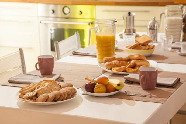 schöne heimat frühstück mit saft, kaffee, croissants, frischem obst und biscuits.jpg - crostata stock-fotos und bilder
