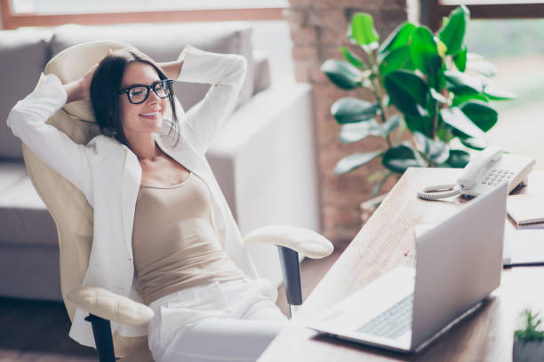 nice, independent, cute woman in white suit, formal wear, glasses sitting on chair at her desk in office, holding arms behind the head with close eyes, thinking about holidays, vacation - fare una pausa foto e immagini stock