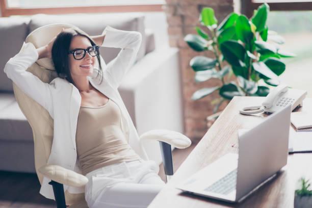 trevlig, oberoende, söt kvinna i vit kostym, formella glasögon, sitter på stol vid sitt skrivbord på kontoret, hålla armarna bakom huvudet med nära ögon, funderar på semester, semester - ta en paus bildbanksfoton och bilder