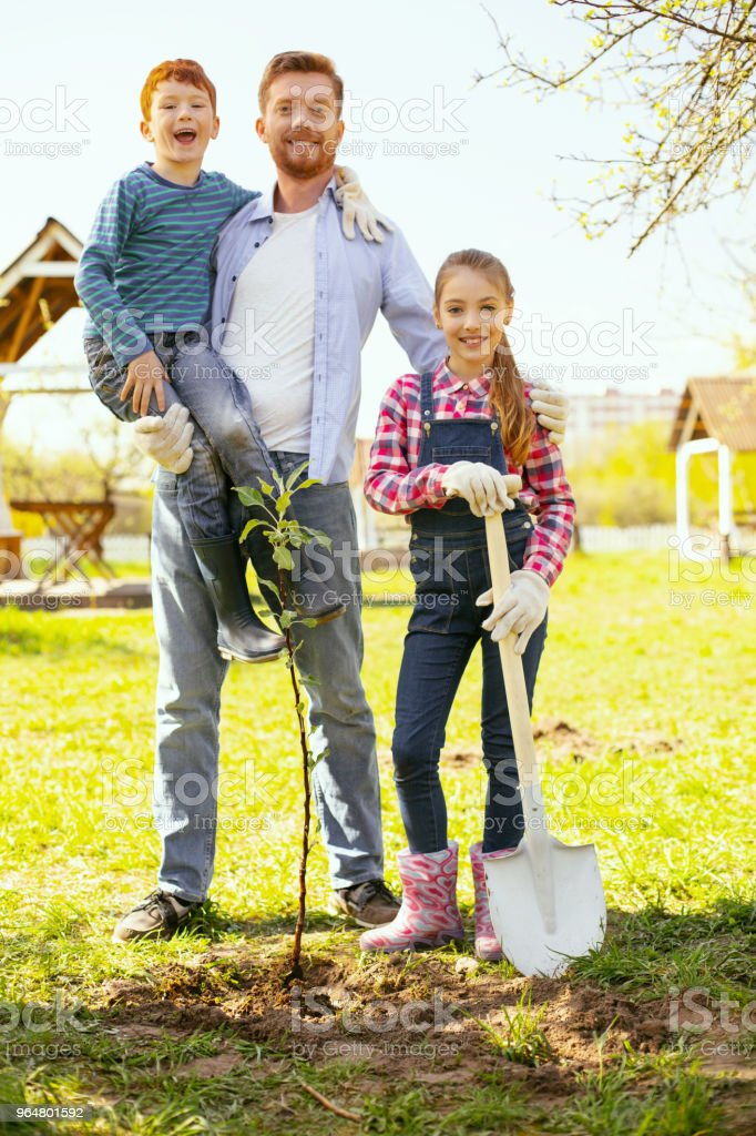 Nice joyful man standing with his children royalty-free stock photo