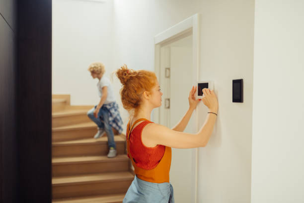 Nice joyful woman pressing the sensory panel Smart house. Nice joyful woman looking at the sensory panel while pressing it smart thermostat stock pictures, royalty-free photos & images