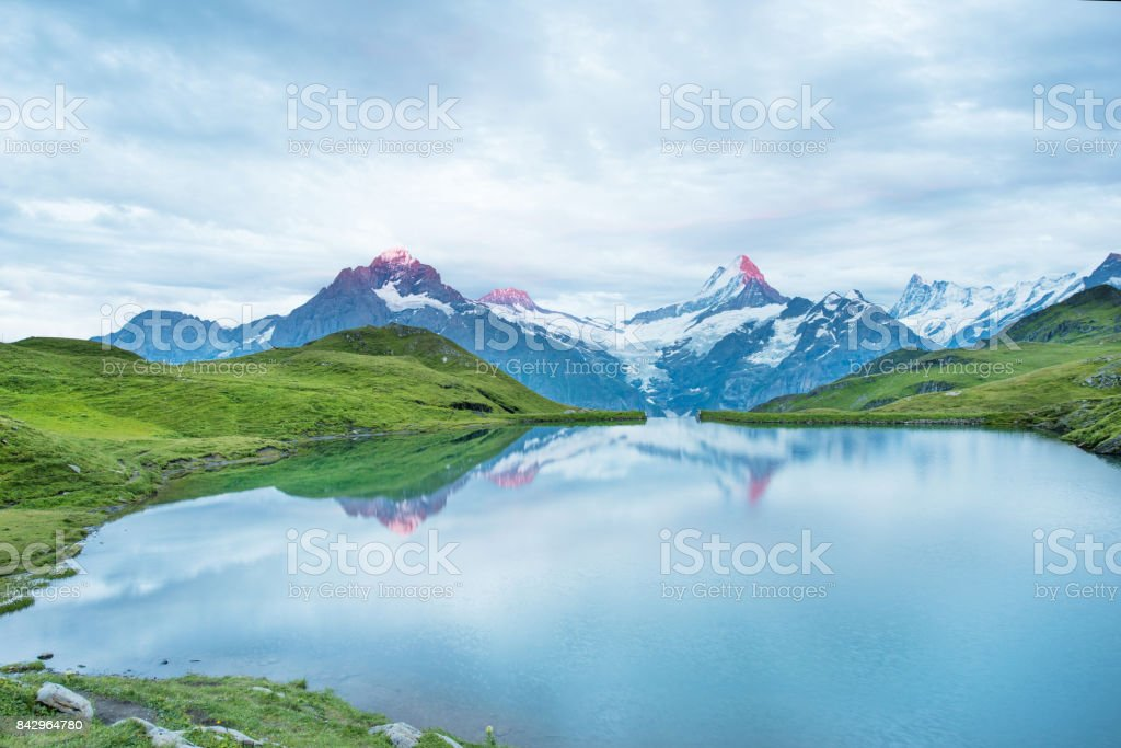 Nice landscape at sunrise over the lake in the Swiss Alps, Europe. Wetterhorn, Schreckhorn, Finsteraarhorn et Bachsee. ( relaxation, harmony, anti-stress - concept). stock photo