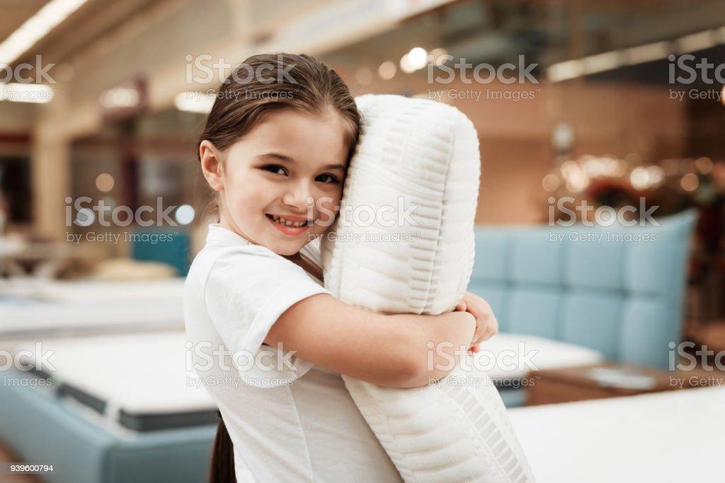 Nice little girl hugs pillow in store of orthopedic mattresses....