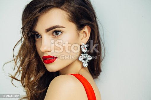 Portrait of a nice looking woman with beautiful earings. Professional make-up and hairstyle.