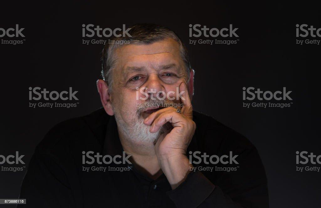 Nice low key portrait of bearded Caucasian senior man stock photo