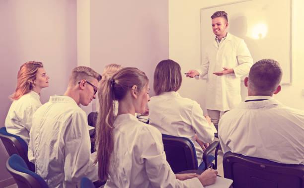 schöne männliche schüler beantwortung in der nähe von whiteboard - lautsprecher test stock-fotos und bilder