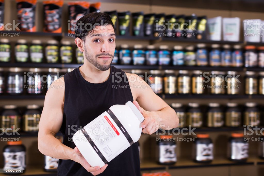 Nice man holding sport nutrition products stock photo