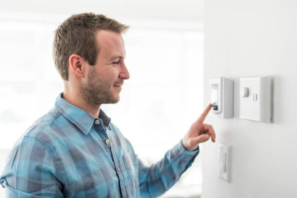 een aardige man stel de thermostaat in huis. - bijstellen stockfoto's en -beelden