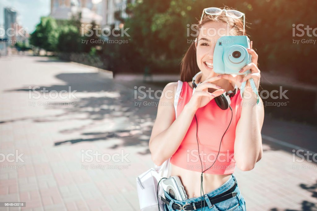 Nice melomanic girl is looking at camera though lenz of her camera. She is smiling. Girl has headphons around her neck and music player close to her body. She is happy royalty-free stock photo
