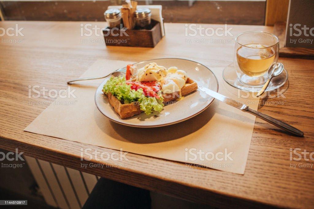 Fin bild på plåt som är på trä bord. Det finns våffla med grönsaker på den. - Royaltyfri Aperitif - Måltid Bildbanksbilder