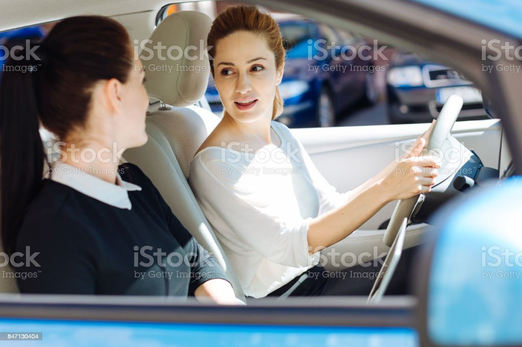 Nice pleasant businesswoman looking at her colleague stock photo