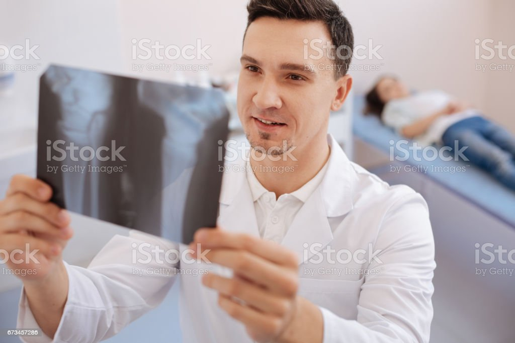Nice pleasant doctor holding an X ray photo stock photo