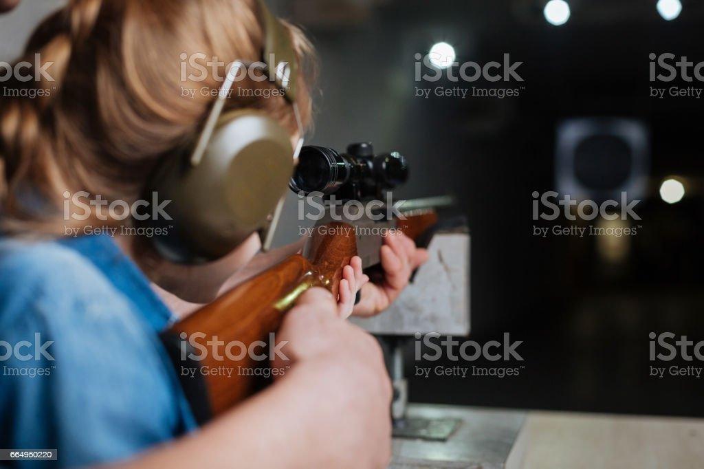 Nice pleasant girl developing her shooting skills stock photo