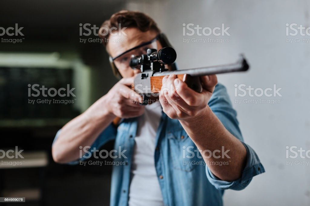 Nice pleasant man developing his shooting skills stock photo