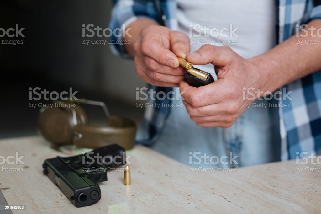 Nice pleasant man putting a bullet into the cartridge clip stock photo