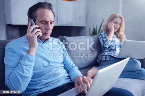 Distance communication. Nice pleasant handsome man holding a cell phone and making a call while working on the laptop
