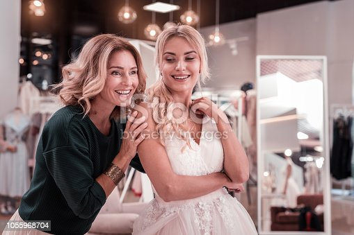 Time with family. Nice pleasant mother and daughter smiling while being together in the wedding boutique