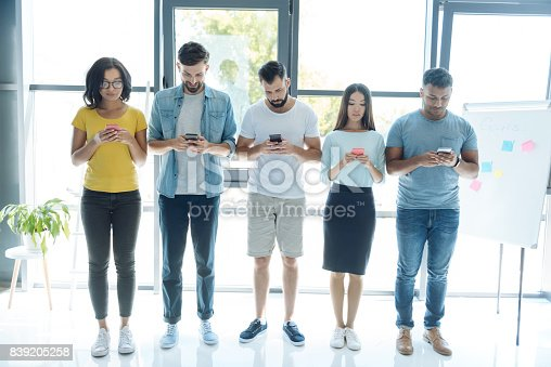 Modern generation. Nice good looking pleasant people standing in a row and focusing on their smartphones while presenting modern generation