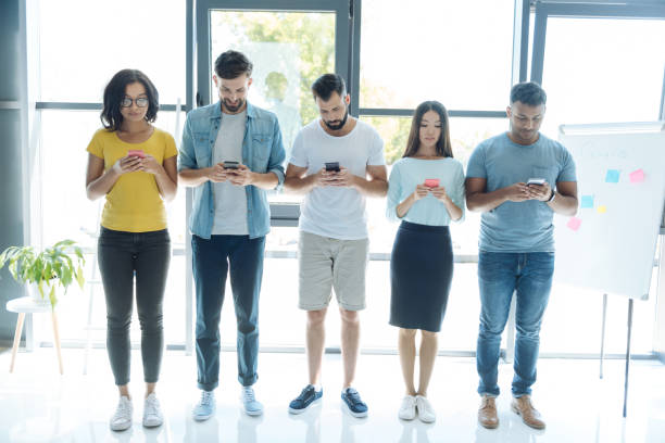 Nice pleasant people standing in a row Modern generation. Nice good looking pleasant people standing in a row and focusing on their smartphones while presenting modern generation generation z stock pictures, royalty-free photos & images